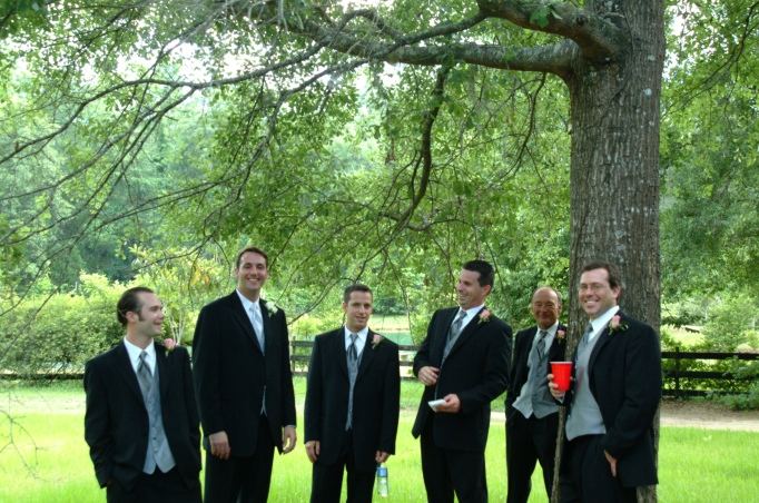 Groomsmen talking under tree